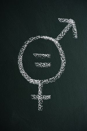 A symbol for gender equality drawn with chalk on a dark green chalkboard