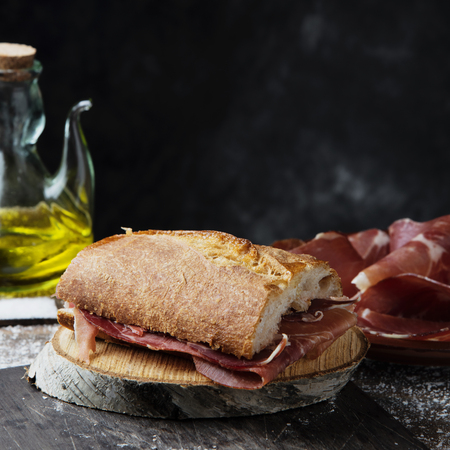 Closeup of a typical spanish  a serrano ham sandwich, on a rustic wooden table