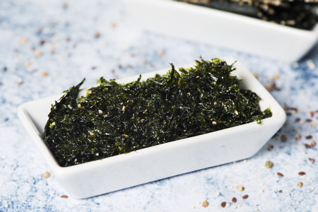 Snacks made with seaweed and sesame seeds on a rectangular white ceramic bowl