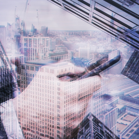 A multiple exposure of a financial district and a businessman using a smartphone