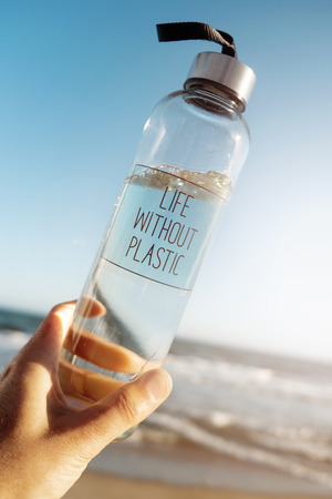 Closeup of a caucasian man holding a glass reusable water bottle with the text life without plastic written