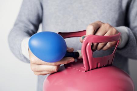 Primo piano di un uomo caucasico, che indossa un maglione grigio, che gonfia un palloncino blu con elio da un cilindro rosa