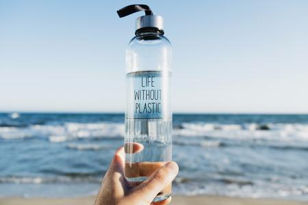 Zbliżenie kaukaski mężczyzna trzymający szklaną butelkę wody wielokrotnego użytku z tekstem życia bez napisanego plastiku