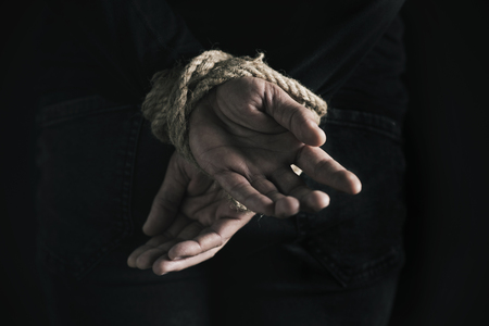 Closeup rear view of a man with his hands tied behind his back with rope