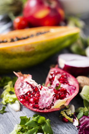 closeup of a halved pomegranate on a gray rustic wooden table full of different fruits and vegetables, such as half papaya, chopped lettuce, a purple onion or a red apple