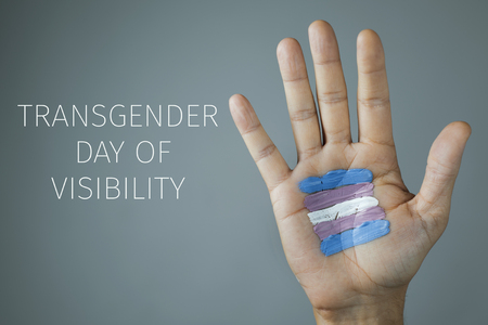 the text day of visibility and the palm of the hand of a young caucasian person with a flag painted in it, on a gray background
