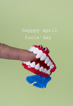 una divertente dentiera che morde l'indice di un giovane uomo e il testo buon pesce d'aprile, su sfondo verde