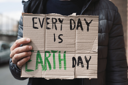 closeup of a young caucasian man, on the street, showing a brown cardboard signboard with the text every day is Earth day handwritten in it Stock Photo