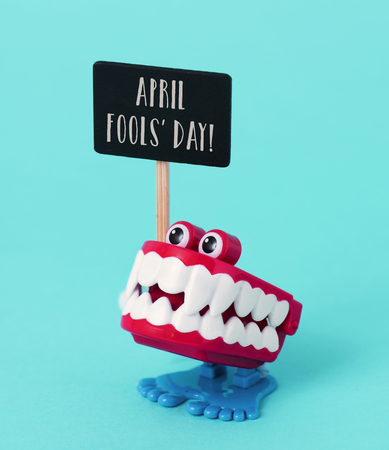 a funny denture with a black signboard with the text april fools day written in it, on a blue background