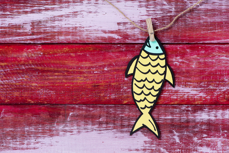 a homemade paper fish, made by myself, as a popular prank for april fools day in countries such as Italy, France, Belgium, Netherlands, Switzerland or Canada hanging from a rope with a clothespin 스톡 콘텐츠 - 120705758