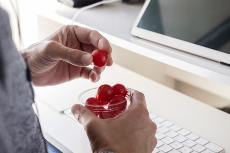 closeup of a young caucasian man eating cherry tomatoes from a plastic container sitting at his desk at the office