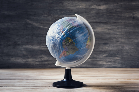 closeup of a world globe wrapped in plastic, on a white rustic wooden table, against a gray rustic background