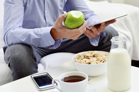 closeup of a young caucasian businessman checking his tablet and his smartphone sitting next to a table set for breakfast, with a cup of coffee, an apple and a bowl with cereals
