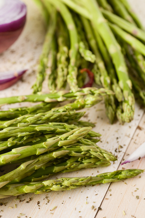 closeup of two bunches of raw wild asparagus on a white rustic wooden table or countertop