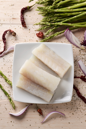 high angle view of some slices of raw codfish on a white ceramic plate, some wild asparagus, some chili peppers and some slices of purple onion, on a white rustic wooden table Archivio Fotografico
