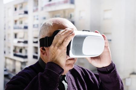closeup of an old caucasian man using a virtual reality headset outdoors Stockfoto