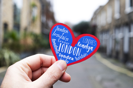closeup of the hand of a young caucasian man holding a heart, with the word London in different languages, in an old street in a residential neighborhood in London, United Kingdom 스톡 콘텐츠