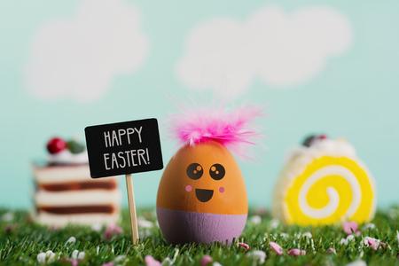un œuf de pâques fait à la main, avec un visage mignon, sur l'herbe, à côté d'un panneau noir avec le texte joyeuses pâques écrit dedans, quelques morceaux de gâteaux colorés et un ciel avec des nuages en arrière-plan