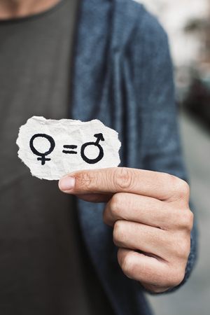 closeup of a caucasian person on the street showing a piece of paper with the depiction of the gender equality drawn in it Banque d'images