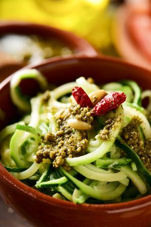 closeup of an earthenware bowl with vegan zucchini spaghetti with italian pesto sauce on a table