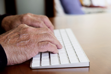 closeup of an old caucasian man sitting at an elegant wooden table typing in a keyboard