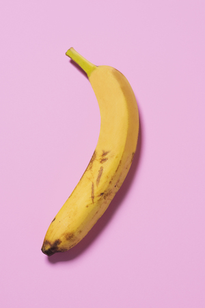 a banana on a pink background, half as it is actually, and half after a treatment, depicting the before and after a cosmetic surgery or beauty treatment, or before and after a digital retouching Archivio Fotografico