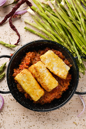 high angle view of a frying pan with bacalao a la vizcaina, a typical spanish recipe of codfish, with tomato, garlic, onion and red pepper, on a rustic wooden table, next to some green asparagus Archivio Fotografico