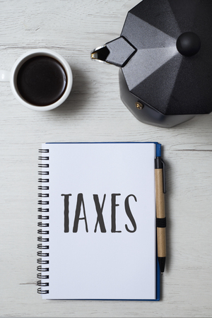 high angle view of a notebook with the word taxes written in first page, a pair of black plastic rimmed eyeglasses, a cup of coffee and a moka pot on a white wooden table
