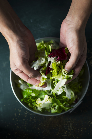 closeup of a young caucasian man about to prepare a salad with a mix of different salad leaves, like romaine lettuce, endive or arugula, in a rustic metal dish, on a dark green table Archivio Fotografico