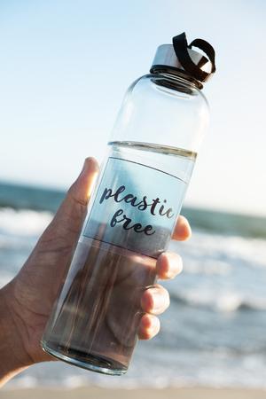 Primer plano de un hombre caucásico sosteniendo una botella de agua de vidrio reutilizable con el texto escrito libre de plástico, en la playa, con el océano de fondo Foto de archivo