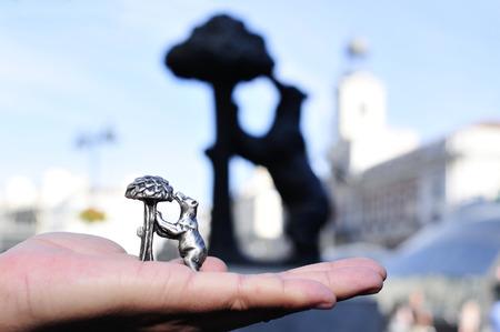 ktoś trzyma pamiątkową reprodukcję popularnego zabytku El Oso y el Madrono z prawdziwym pomnikiem w tle, w Madrycie, Hiszpania