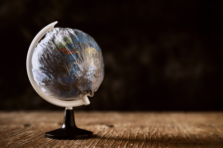 a world globe wrapped in a dirty plastic, on a rustic wooden surface, against a dark background, depicting the air pollution, the excess of plastic waste on our planet or the greenhouse effect Banque d'images