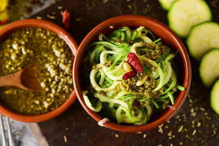 high angle view of some earthenware bowls with zucchini spaghetti and italian pesto sauce, nex to some slices of raw zucchini on a rustic wooden table