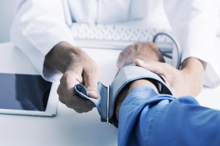 백인 의사 남자가 흰 코트를 입고 혈압계를 들고 의사 책상에 앉아 있는 백인 노인 환자의 혈압을 측정하려고 합니다.