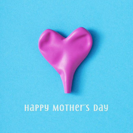 a deflated pink heart-shaped balloon and the text happy mothers day on a blue background