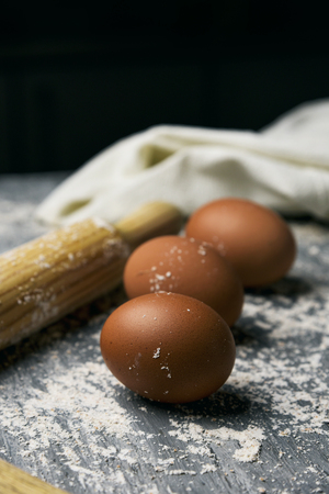 closeup of some brown eggs and a wooden rolling pin on a rustic table sprinkled with flour, against a black background with some blank space on top Фото со стока