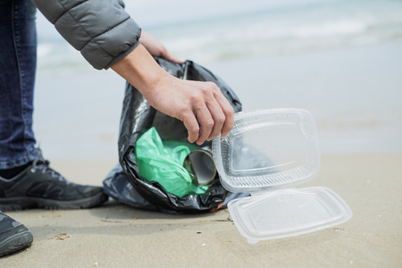 closeup of a caucasian man collecting garbage on a lonely beach, next to the water, as an action to clean the natural environment