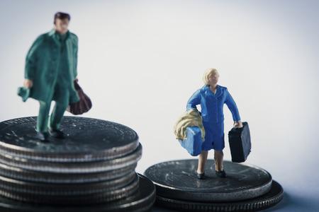 Primer plano de una mujer en miniatura y un hombre en miniatura en la parte superior de dos pilas diferentes de monedas de dólar estadounidense, el hombre en la pila más alta y la mujer en la pila más corta, para representar la brecha salarial de género.