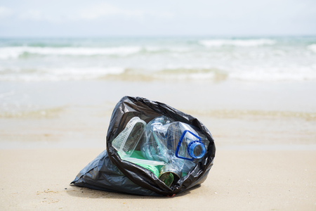 closeup of a gray plastic bag with collected garbage on the sand of a lonely beach, next to the water, in the background