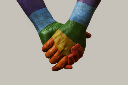 closeup of two men holding hands, painted as the rainbow flag, against an off-white background Stock Photo