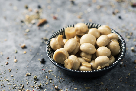 closeup of some cooked mini common mushrooms in a black and white bowl placed on a stone surface, sprinkled with different spices
