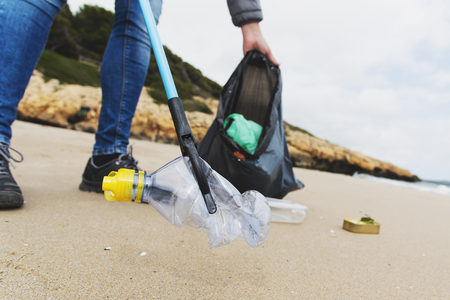 closeup of a caucasian man collecting garbage with a trash grabber stick, on a lonely beach, as an action to clean the natural environment