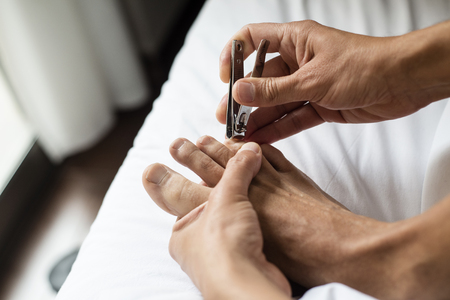 closeup of a young caucasian man, sitting on a bed dressed with white linen, cutting his toenails with a nail clipper Imagens