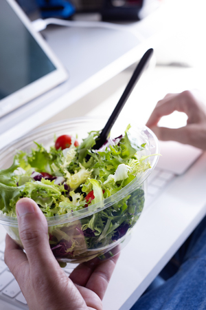 closeup of a young caucasian man eating a salad from a plastic container sitting at his desk at the office
