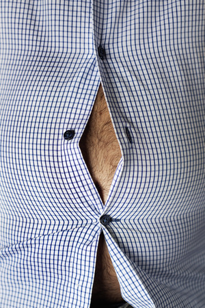 closeup of a caucasian man, with a hairy beer belly seen through the buttons of his tight shirt