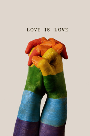 the clasped hands of two men, painted as the rainbow flag, and the love text is love against an off-white background