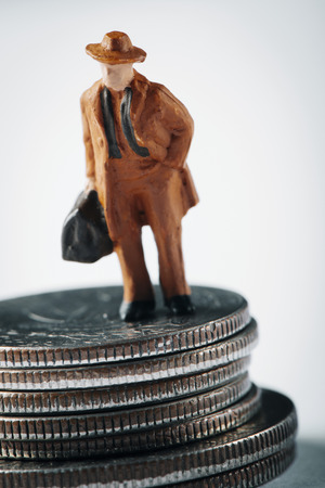 closeup of a miniature man, carrying a suitcase, on the top of a pile of dollar coins Stock Photo