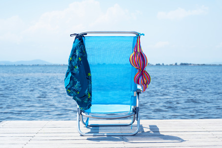 a colorful bikini and a pair of blue swimming trunks drying on a blue deck chair, on a wooden pier, next to the water Banque d'images - 122708528