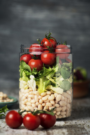 closeup of a jar salad, with cherry tomatoes, a mix of different leaf vegetables, and cooked white beans, on a rustic wooden table against a gray background Archivio Fotografico