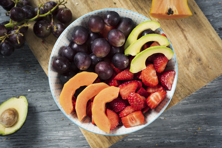 high angle view of a ceramic bowl with a fruit salad, made with avocado, papaya, strawberries, grapes and blueberries on a chopping board, placed on a gray rustic wooden table